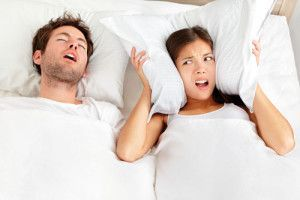 Snoring man. Couple in bed, man snoring and woman can not sleep, covering ears with pillow for snore noise. Young interracial couple, Asian woman, Caucasian man sleeping in bed at home.