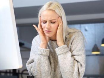 Migrenowy ból głowy. Zmęczona kobieta pracuje przykomputerze