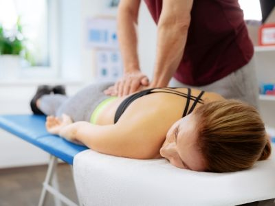 Pleasant relaxed woman receiving aback massage